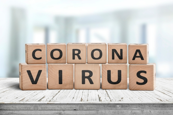 Corona virus alert message on a worn wooden desk